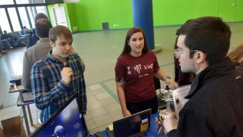 Alex Davie and Lexi Serwon discuss research with a visitor to biophysics table